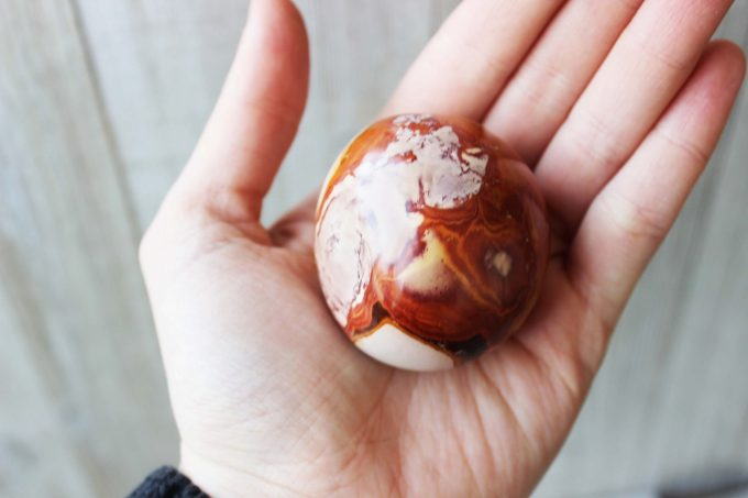 Natural polychrome jasper from Madagascar polished into a palm stone for meditation